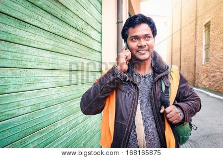 Young indian travel man making phone call walking on the street holding bag at winter time - Handsome bangladeshi guy looking up using mobile smiling outdoors - Communication concept with copy space
