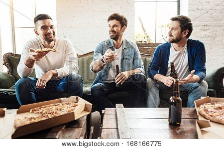 Tasty food. Handsome good looking smiling man holding a slice of pizza and intending to eat it while watching TV with his friends