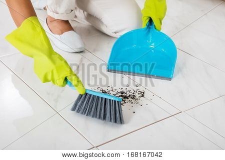 Close-up Of Person Hand Wearing Gloves Using Broom And Dustpan On The Floor