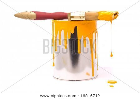 Can of yellow paint and professional brush on a white