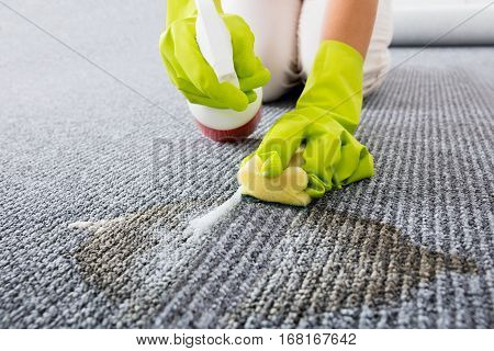 Close-up Of Person Hand Wearing Gloves Spraying Detergent On Grey Carpet To Remove Stains