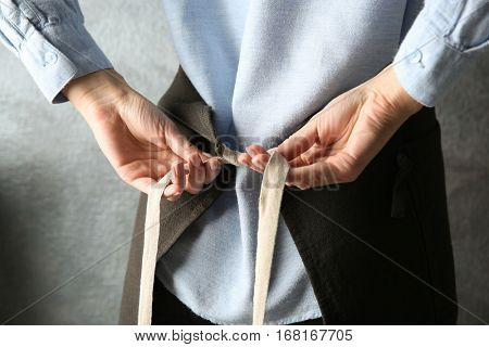 Woman  tying up her apron around the waist