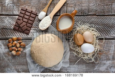Fresh dough, eggs and milk on wooden background