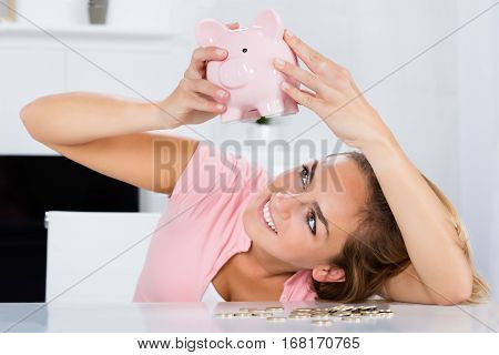 Young Happy Woman Emptying Her Piggybank Savings With Less Than Expected At Home