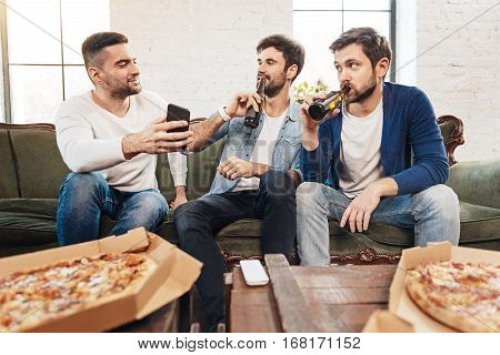 Male company. Handsome pleasant brutal men looking at the smartphone screen and taking a sip of beer while resting at home