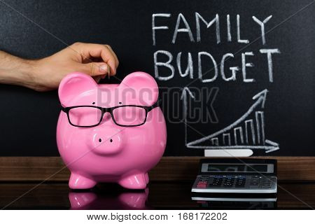 A Person Hand Saving Money In Piggybank For Family Budget In Front Of Blackboard
