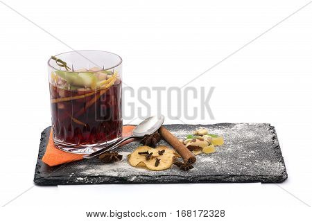 Mulled wine and spices served on mica. Coctail in the glass and beautiful serving dishes with cinnamon sticks, oranges and small candies close-up in isolated white background close-up