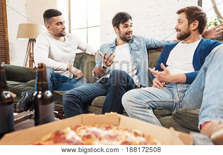 Interesting discussion. Delighted handsome male friends sitting comfortably on the sofa and gesticulating while having an interesting discussion