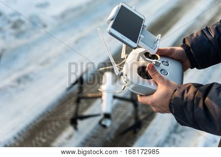 Man with remote control prepare white drone with digital camera for start flying in winter weather with snow