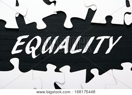 The word Equality in white text on a blackboard with a border of jigsaw puzzle pieces as a concept for solving problems of equal rights