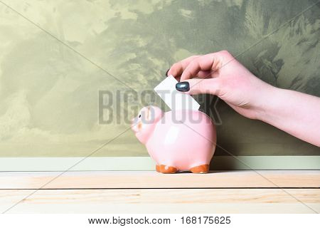 pink piggy bank or moneybox with paper in female hand as savings symbol on wooden board on grey textured wall background copy space