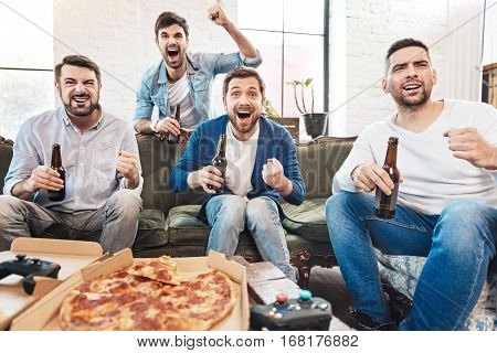 Watching a football match. Nice happy delighted men watching TV and drinking beer while being happy for their football team