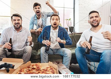 Football fans. Happy handsome attractive men drinking beer and watching football while supporting their football team