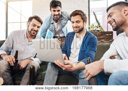 Electronic device. Handsome delighted bearded man holding a laptop and using the touchpad while showing something to his friends
