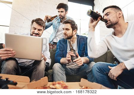 Drink for true men. Handsome brutal nice man taking a sip of beer and looking at the laptop screen while sitting on the sofa with his friends
