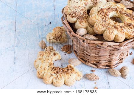 Almonds and  ring cookies, strewed with chopped nuts, in  basket on an old wooden table.
