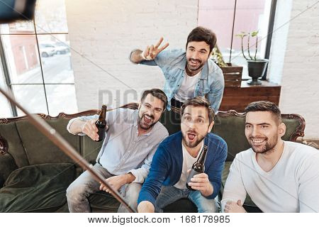 Memorable moments. Delighted elated positive men using a selfie stick and smiling while taking a selfie