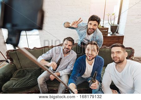 Time for photos. Handsome happy male friends looking into the smartphone camera and smiling while posing for a selfie