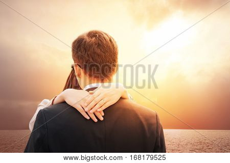 Romantic couple in love on Happy valentines day. Lovers back hugging and standing on tropical beach with dramatic sunset sky background. Girl wearing engagement heart shape ring. Relationship concept.