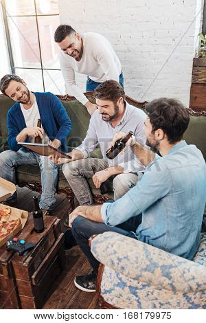 At the weekends. Handsome cheerful positive men having beer and enjoying their time together resting at the weekends