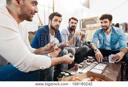 I bet. Handsome cheerful pleasant man holding chips and making a bet while playing poker with his friends poster