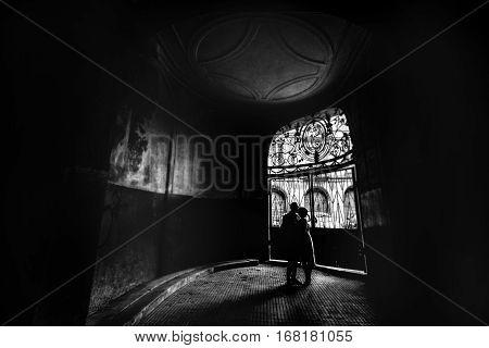 Romantic Couple Holding Hands In Dark Old Street Hallway B&w