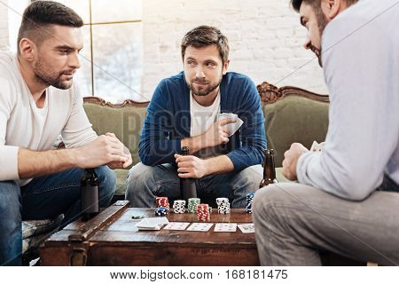 Dishonest play. Attractive good looking bearded man holding his cards and having a sly look while playing the poker game
