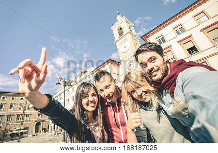 Group of cool multiculture tourists friends having fun taking selfie in old town tour - Travel lifestyle concept with happy people wandering around city landmarks - Contrast desaturated retro filter