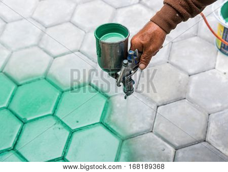 The Masonry Worker Painting Paving Block By Color Air Brush And Hand Brush