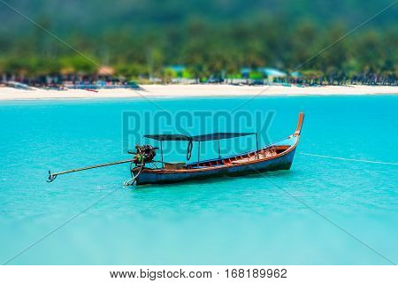 The Tilt Shift Of Fishing Boat In The Blue Sea At Coast Of  Thailand