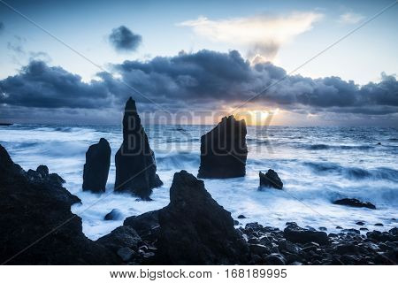A remote beach in Iceland shows sharp rocky reefs protruding 20 feet out of the shallow water during a sunset.