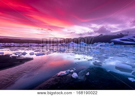 Icebergs in Jokulsarlon glacial lagoon during a vibrant red sunset rests motionless as it is framed by cold ocean water.