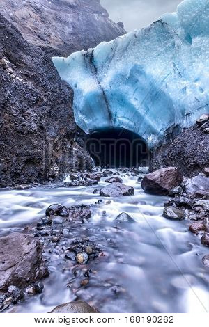 An ice cave in Iceland formed below a glacier is melting and forming a river lowing through the mouth of the cave.