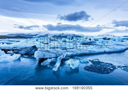 Icebergs along the shore of Jokulsarlon glacial lagoon during a blue overcast day rest motionless while framed by cold ocean water.