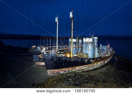 Two abandoned whaling ships rest on a remote beach after Iceland scrapped their whaling program. Ships are light painted at night with heavy rain pouring through the blue light.