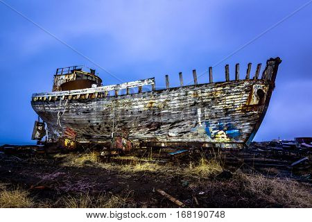 An old abandoned whaling ship from the early 1900's rests on a remote shipyard beach as it rots, exposing the ship's wooden ribs and hull infrastructure. Image was shot at night and light painted.