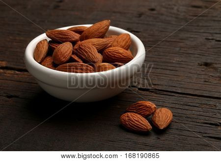 Group of delicious almonds in a bowl over a wooden background