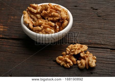 Group of delicious nuts in a bowl over a wooden background