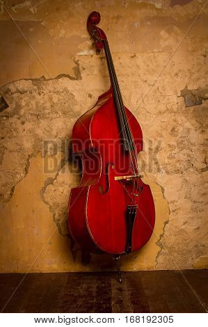 the double bass is leaning against the wall potrasenoy