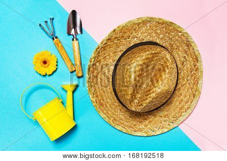 Gardening Spring Vacation or Summer Concept. Straw Hat with Gardening Tools on Colored Background. Flat Lay. Minimalistic Concept.