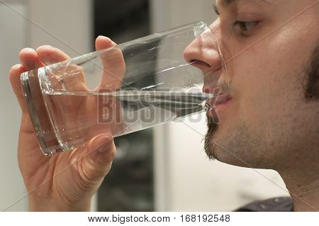 Close-up of a young man drinking a glass of water