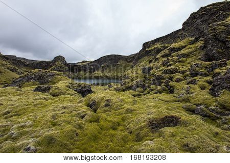 Laki crater lake Tjarnargigur on Iceland with green moss