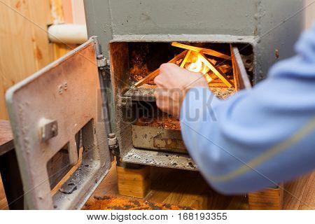 Man make a fire in Solid bio fuel boiler