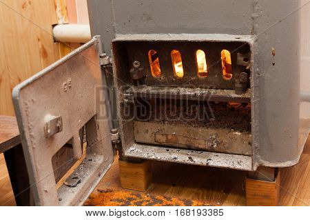Wood burning inside the Solid bio fuel boiler. Renewable source of energy. green environmentally friendly fuel. Old warm cozy burning fire in a fireplace close up