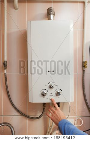 Man hand switch Gas water heater to hot water