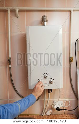 Men hand regulate the power of hot water in Gas water heater