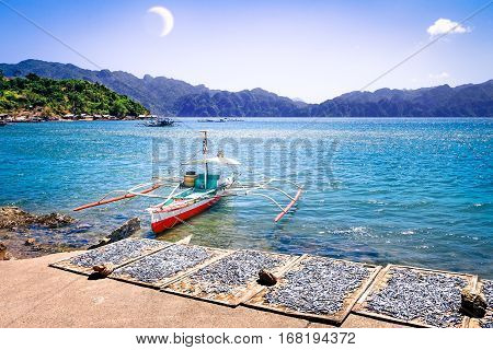 Philippines Islands seascape with old outrigger boat and fresh drying fish on small harbor at Coron blue lagoon after sunset - Travel concept of nature panorama at nautical twilight time