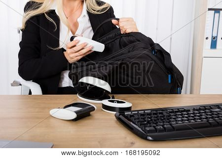 Close-up Of A Businesswoman Stealing A Stapler At Office Desk
