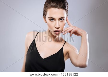 Using what I have. Creative enthusiastic pretty girl finding fresh uncanny poses while approaching her face with her hand and wearing black silk top