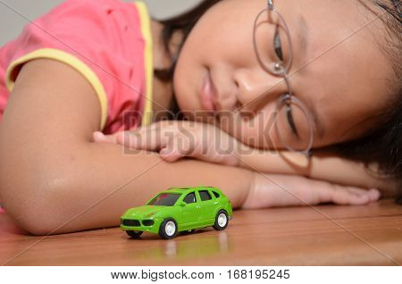 SINGAPORE - JAN 28 2017: Young girl with green toy car. Focus on car.